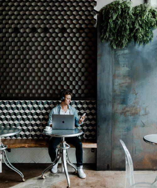 Membre agence Pilowa avec chemise en jean devant son ordinateur